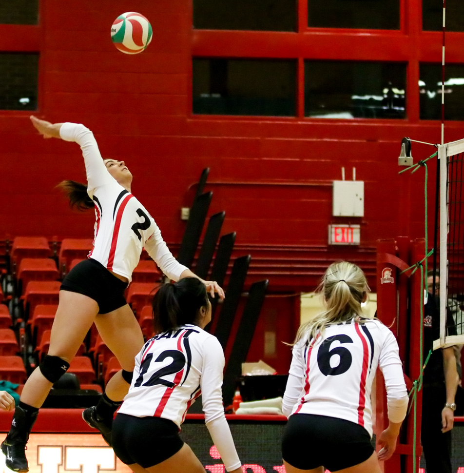 Is it Bird? Is it a Plane?: SAIT Trojans outside hitter Megan Brennan, left, prepares to spike the ball against the Olds Broncos in women's volleyball in the SAIT Campus Centre gym in Calgary on Saturday, Feb. 6, 2016. The Broncos won Alberta Colleges Athletics Conference game 3-1 against the Trojans. (Photo by Sydney Elton/The Press)