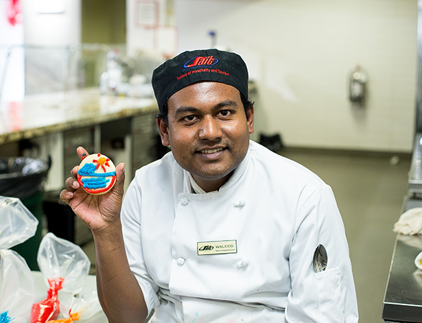 Cookie maker and decorator : Waleed Sabur, a first year of the Baking and Pastry Arts program at SAIT holds a cookie he decorates during the YYC Doors Open public event at the SAIT culinary campus Saturday afternoon in September 24, 2016 in Calgary Alta. Waleed Sabur is an international contract student worker that volunteers for a lot of the events happen. (Photo by Sareenah Singh/The Press)