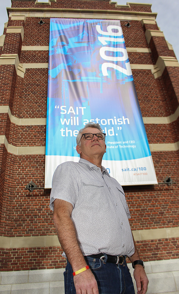 Standing Proud: Marc Bussiere, an instructor for Architecture and Technology at SAIT poses in front of a SAIT 100th banner outside Heritage Hall on Sept. 26, 2016. SAIT 100 is an upcoming celebration of the polytechnic institution's century marking anniversary. (Photo by Shane Weaver/The Press)
