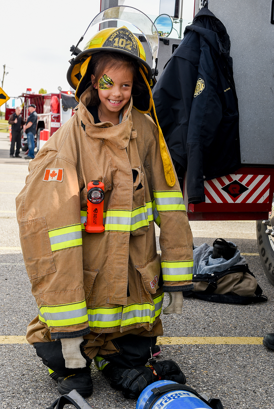 six-year-old Gabriella Vanenk tries on a Rocky View County Fire and Rescue fireman's uniform at the Springbank Old Tyme Fall Fair on Saturday, Sept. 10, 2016. There was a climbing wall, face painting and lots of other activities to ensure a good time for kids. (Photo by Jeremy Ash/The Press)