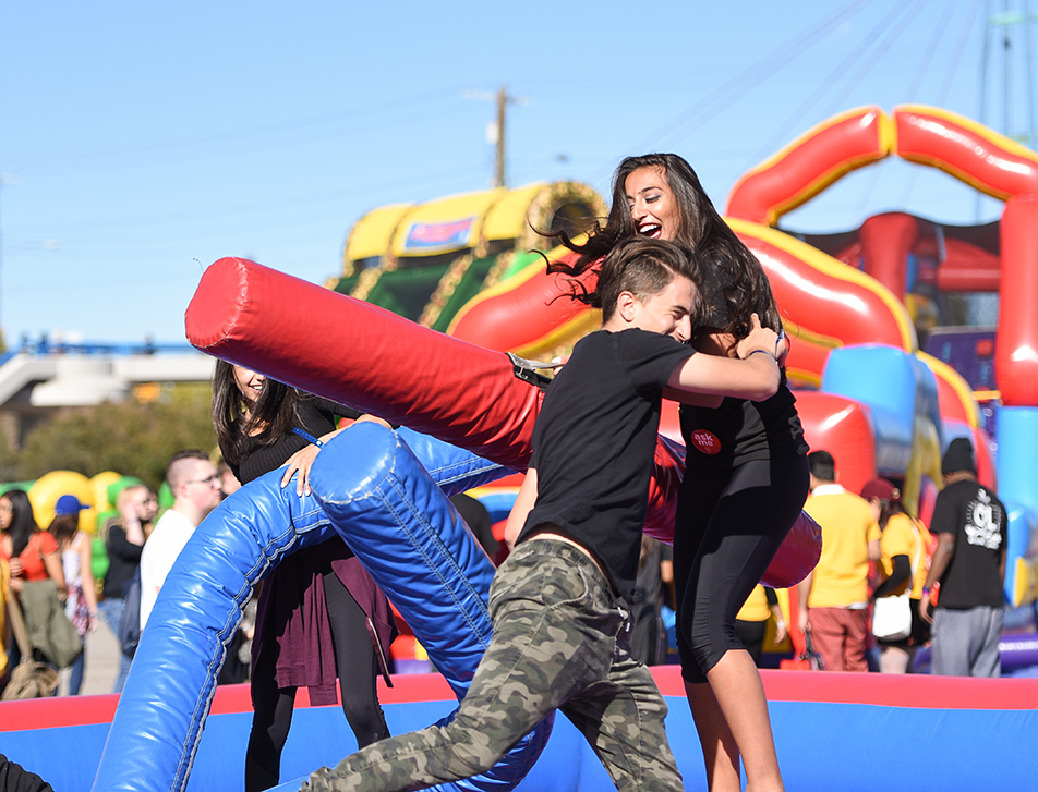 Janine Jomaa, right, takes a playful tackle from boyfriend, Harwinder Giwal, during a game of Paddle Fighting at the McMahon Stadium in Calgary on Friday, Sept. 9, 2016. The event was part of the University of Calgary's New Student Orientation Tailgate Party. (Photo by Cyril Brabant/The Press)