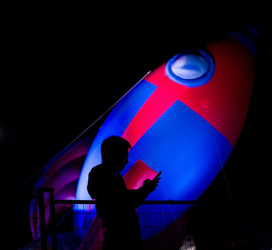 Illuminated Rocket: Galvin Chung takes a photo in front of an inflatable rocket ship during Beakerhead's Beakernight at McDougall Park in Calgary. (Photo by Ashley Orzel/The Press)