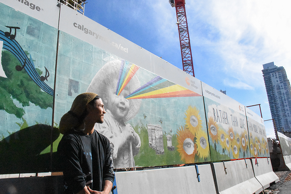 Mural Art: Kai Cabodyna stands in front of his artwork on a temporary wall in Calgary. The mural will be up until construction of the new Central Library is finished in 2018. (Photo by Foster Modesette/The Press)