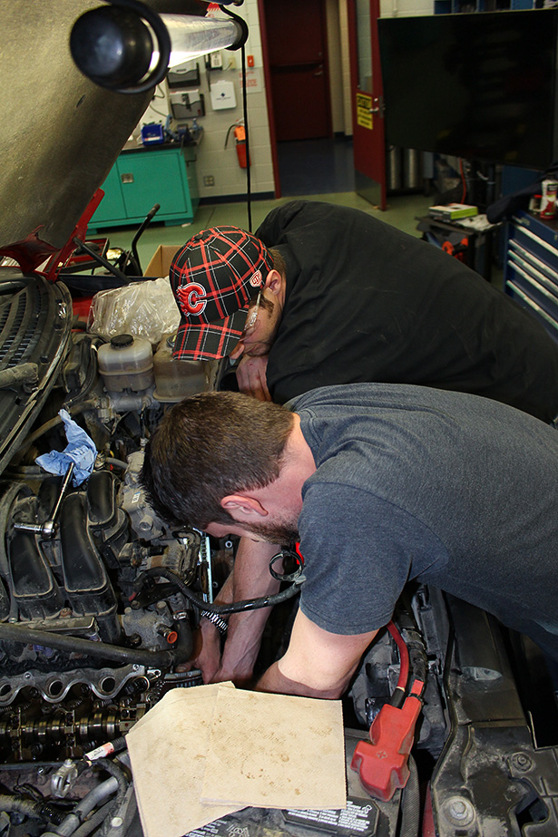 Teamwork: Derrick Rust, top, and Garrett Farlick work together on an automotive project. Both students in their second year of the Ford ASSET (Automotive Student Service Educational Training) program at SAIT.