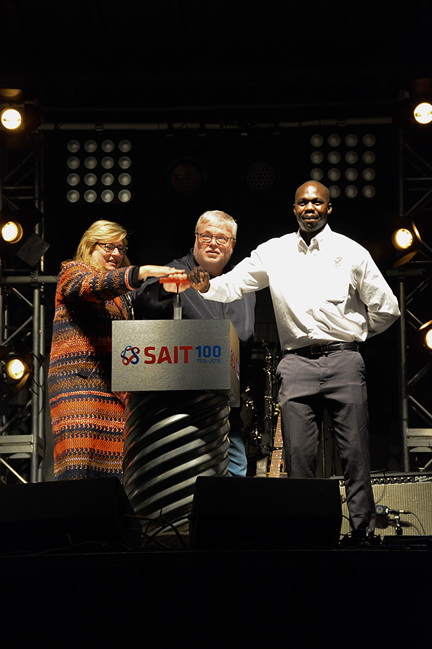 Ka-boom: Left to right: Heather Culbert, Chair of the SAIT Board of Governors, Dr. David Ross, President and C.E.O. and Gar Gar, SAITSA President press the plunger to begin the fireworks at SAIT in Calgary on Sunday, Oct. 16, 2016. Events filled all the corners of campus, among them were the 1966 time capsule reveal, the cutting of SAIT's birthday cake, and a performance by Dan Mangan on the Cohos Common soccer field right before the fireworks finale. (Photo by Jolisa Tweedie/The Press)