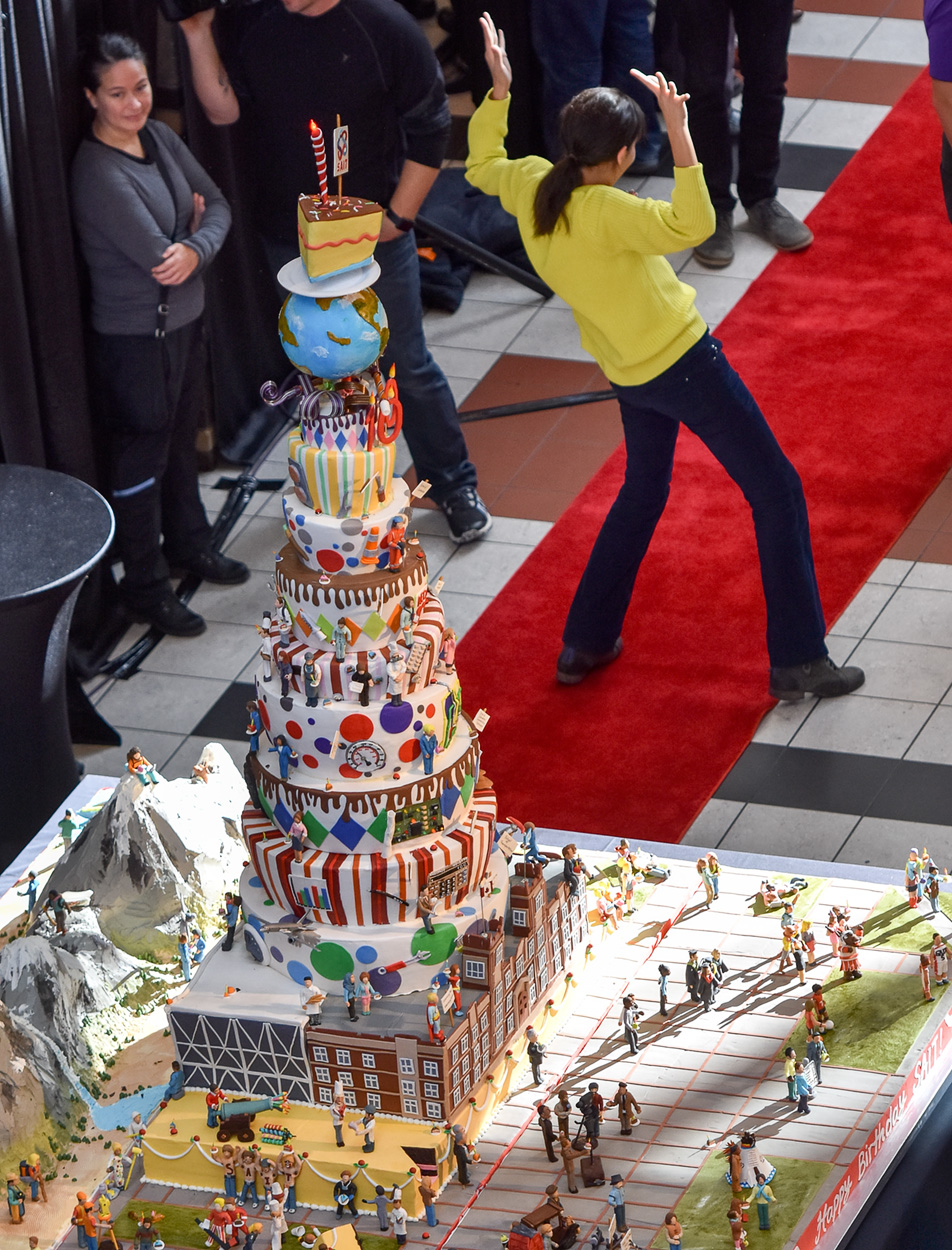 Comic Confection: A partygoer, right, poses for a photo with SAIT's 100th birthday cake in the Stan Grad Centre. (Photo by Jeremy Ash/ The Press)