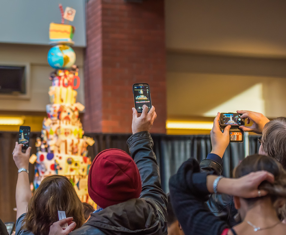Phoning it In: Birthday cake spectators take pictures of the 14-layer treat in the Stan Grad Centre. (Photo by Terri Huxley/The Press)