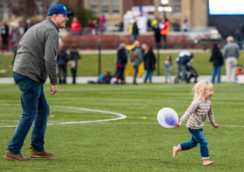 Cheerful Chase: A man and child play on Cohos Commons Field. (Photo by Terri Huxley/The Press)
