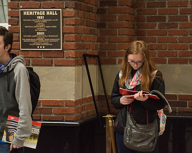 Reading up: A high school student reads up on SAIT's various programs in the Stan Grad building on Friday, Oct. 28, 2016. SAIT's open house draws a number of people, including many high school students, who are interested in developing a practical education. (Photo by Kyle Bridge/The Press)