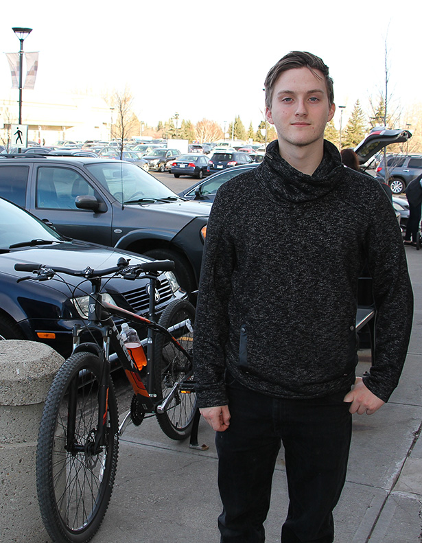 Biking Barista: Tony Tascona, a 20-year-old Starbucks barista, poses outside of his workplace in the Glenmore Landing parking lot in Calgary on Tuesday, Nov. 8, 2016. Having only a learner's licence, Tascona depends on bike commuting as his preferred alternative to driving. Tascona said that Calgary's accessible bike paths make it convenient for him to bike anywhere within a 10 to 13 kilometre radius in 30 minutes. (Photo by Laurel McLean/SAIT)