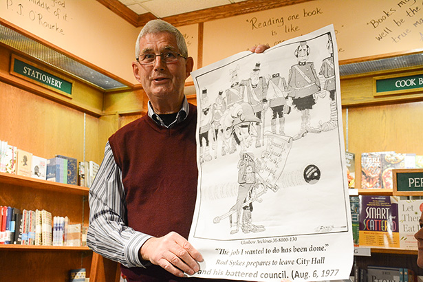 God's Gift to Cartoonists:Andy Marshall shows a political cartoon of former Mayor Rod Sykes at Owl's Nest Books in Calgary on Monday, Nov. 28, 2016. Marshall is a retired reporter for the Calgary Herald. (Photo by Peter Shokeir/The Press)