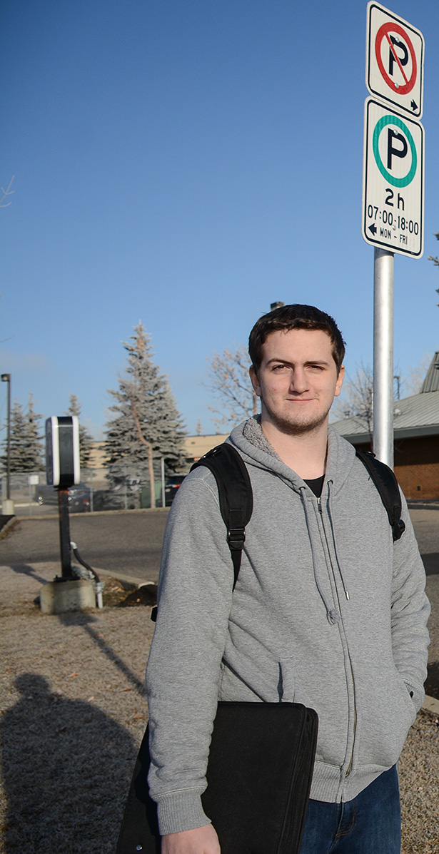 Parking Ticket Roulette: Alexzander Johnson poses near one of the many two-hour parking street signs in the city of Calgary, Alta., on Wednesday, Nov. 30, 2016. Many students choose to risk a ticket on city streets, over paying up in a campus parkade.